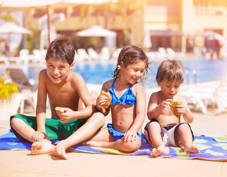 ハッピー子供プールのそばに座って食べたり、クロワッサン、泳いだ後、休憩を持つ 2 つの陽気な兄とかわいい妹のビーチで夏休みを楽しんでいる 写真素材