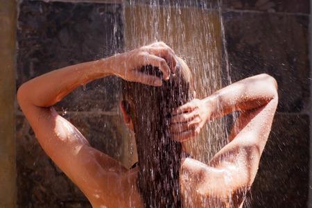 Nő a zuhany alatt, hátoldalán a fiatal női zuhanyozás alatt frissítő víz, egészséges életmód, élvezve időt a luxus üdülőhely