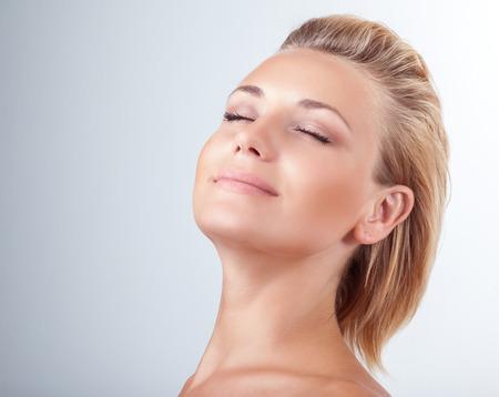 Elégedett nő spa, portré, gyönyörű nő csukott szemmel az öröm fölött világos háttér, természetes kozmetikumok, élvezve nap spa szalon