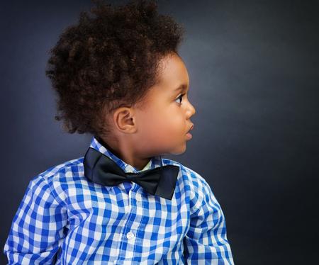 Portrait of cute little African schoolboy with surprise looking in side, over blackboard background, back to school
