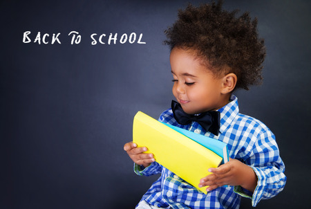 Cute little schoolboy portrait, adorable african child with books in hands over dark background, back to school concept