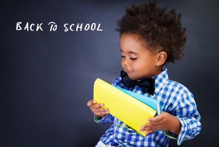 niño escuela: Pequeño retrato Colegial lindo, adorable niño africano con libros en las manos sobre fondo oscuro, de nuevo a concepto de la escuela Foto de archivo