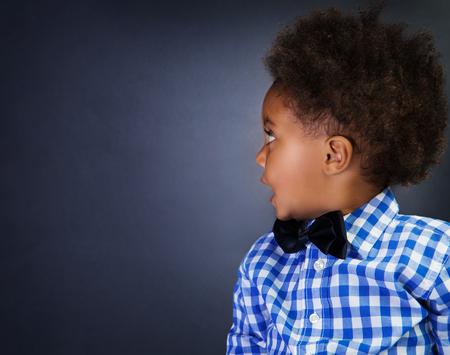 sorprendido: Retrato del pequeño colegial africana linda con sorpresa mira en lado, sobre fondo de pizarra, copia espacio, volver a la escuela