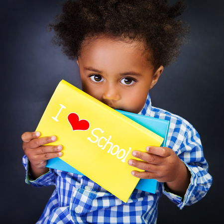 child reading: African schoolboy portrait, cute little child with holding book with text: i love school, on blackboard background, for the first time in first class