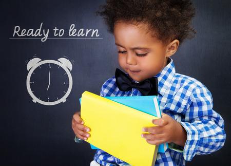 Muchacho afroamericano lindo con libros en las manos en el fondo de la pizarra, niño en edad preescolar adorable listo para aprender en la escuela primaria