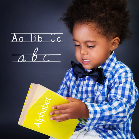 Little boy on language lesson, holding in hands alphabet, learning letters and spelling, preparing to go to first class
