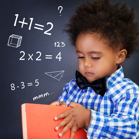 Little boy on math lesson, holding in hands book and standing near blackboard with written mathematical equation, back to school