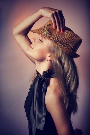 dancing club: Side view of beautiful woman dancing in night club, closing eyes of pleasure, wearing stylish shiny hat, celebrating new year holiday Stock Photo