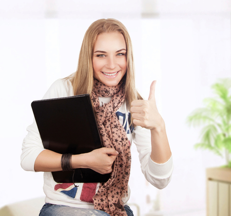nb: Happy student girl sitting at home with laptop, successful lifestyle, gesturing good mood by thumbs up, enjoying education for wireless internet