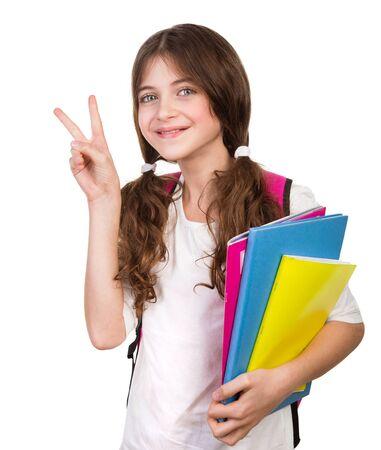 colegiala: Retrato de colegiala linda con el bolso y los libros en las manos aisladas en el fondo blanco, haciendo un gesto de buen humor a mano, volver a la escuela Foto de archivo