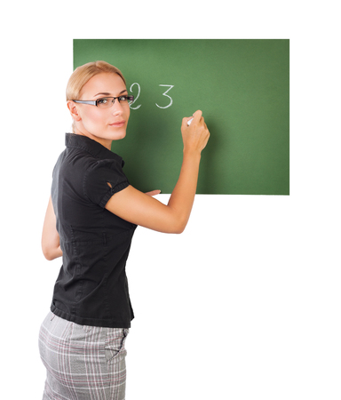 teaching: Young beautiful smart teacher writing numbers on green chalkboard isolated on white background, to teach in an elementary school