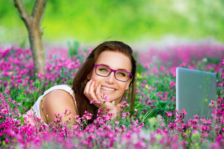 girl lying down: Portrait of beautiful smiling student girl lying down on flowers meadow in the university garden, with pleasure working on laptop outdoors, using wireless internet