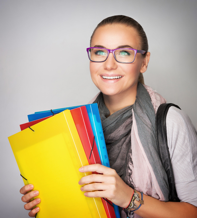 folders: Happy student girl with colorful folders in hands isolated on gray background, enjoying start of school time, high education in the university