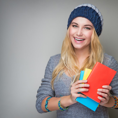 sweater girl: Portrait of beautiful blond student girl wearing stylish hat and holding in hands colorful books standing over gray background