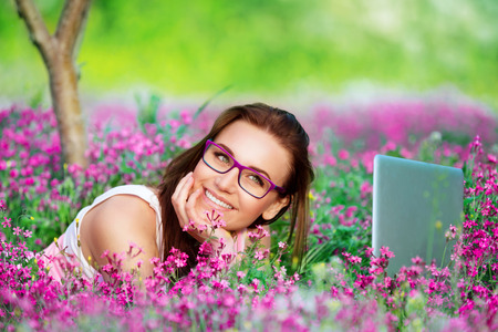 beautiful flowers: Portrait of beautiful smiling student girl lying down on flowers meadow in the university garden, with pleasure working on laptop outdoors, using wireless internet