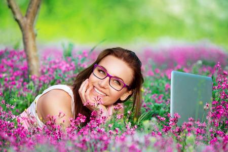 girl lying down: Retrato de la hermosa chica estudiante sonriente acostado en prado flores en el jard�n de la universidad, con el placer de trabajar en la computadora port�til al aire libre, el uso de Internet inal�mbrico
