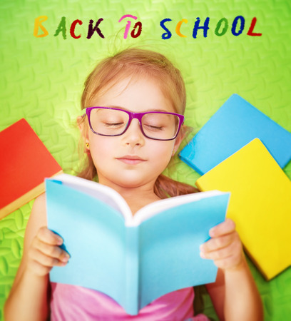 lying down on floor: Cute little schoolgirl doing homework, lying down on the floor at home and reading book, text on the floor : back to school