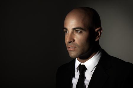 hombre calvo: Retrato de un hombre con traje negro, camisa blanca y corbata elegante, de pie sobre fondo oscuro con copia espacio, traje caro, la moda y el estilo de vida de negocios Foto de archivo