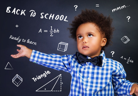 Portrait of smart curly African American schoolboy in the school on mathematics lesson, solving task near blackboard