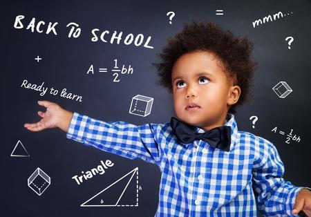 Portret van slimme krullend Afro-Amerikaanse schooljongen in de school over wiskunde les, het oplossen van de taak dichtbij bord