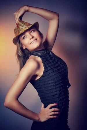 dancing club: Beautiful dancer girl wearing stylish dress and shiny hat over dark background, disco dancing, enjoying time in night club