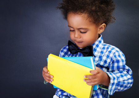 niños negros: Retrato de colegial sosteniendo libros africanos adorables en las manos sobre fondo oscuro, copie el espacio, volver a la escuela Foto de archivo