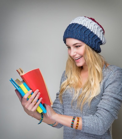 exciting: Portrait of beautiful stylish student girl reading exciting book over gray background, enjoying study in high school