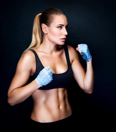 puños cerrados: Muchacha del boxeador en acción, aislado en el fondo negro, haciendo ejercicios en el estudio, el deporte agresivo, saludable y estilo de vida activo Foto de archivo