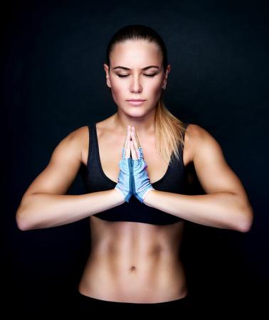 美しい女性は、黒の背景、スポーティーなライフ スタイル、健康的なアクティブな生活にヨガの練習を行うスタジオで瞑想 写真素材 - 45357516