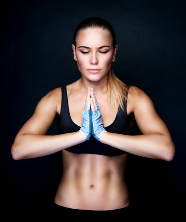 sport background: Beautiful woman meditating in the studio, doing yoga exercises over black background, sportive lifestyle, healthy active life