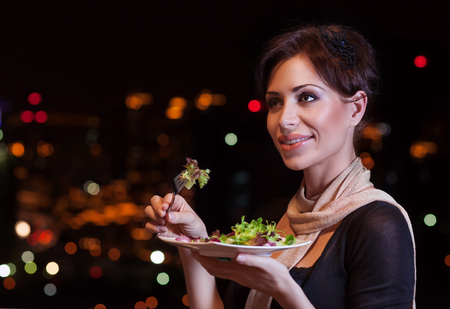 life events: Portrait of beautiful woman eating fresh green salad in the restaurant, having fun on the party, enjoying night life, luxury lifestyle Stock Photo