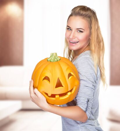 Beautiful blond girl celebrate Halloween holiday at home, holding in hands carved pumpkin face, enjoying happy autumn holiday