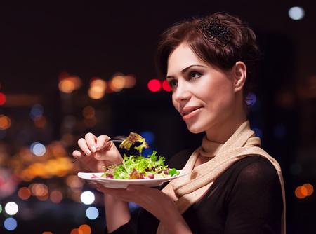 eten: Portret van mooie vrouw het eten van verse groene salade in het restaurant, met plezier op het feest, genieten van het nachtleven, luxe lifestyle