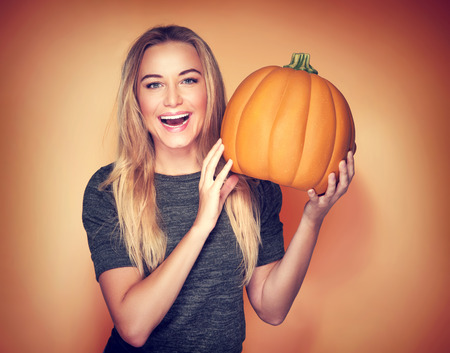 smiling: Portrait of beautiful cheerful woman with pumpkin over orange background, celebrating happy Thanksgiving day