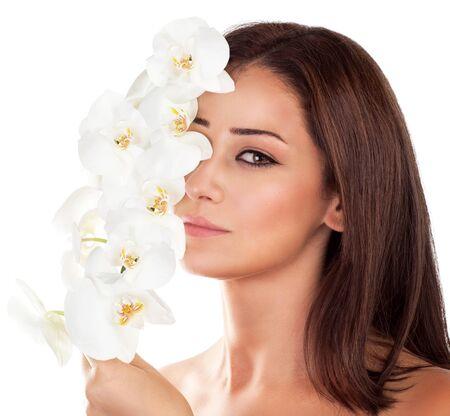 ojos marrones: Retrato de mujer hermosa con flores de las orquídeas frescas en la mitad de la cara aislada en el fondo blanco, la aromaterapia, que disfruta de día en el salón de spa de lujo