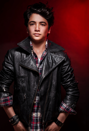 boy beautiful: Handsome boy portrait over red background, wearing leather jacket and stylish shirt, fashionable autumn clothes, funky teens fashion