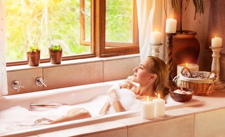 Vrouw baden met plezier, liggend in het bad met schuim en kijkt in het venster, tijd doorbrengen in een luxe kuuroord Stockfoto