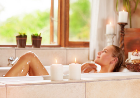woman in bath: Soft focus photo of gentle young woman lying down in bath tub with foam and candle, enjoying spa procedure in the luxury resort