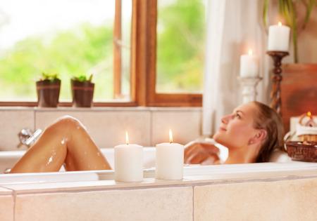 Soft foto de enfoque de la mujer joven gentil acostada en bañera con espuma y la vela, disfrutando el procedimiento del balneario en el centro turístico de lujo Foto de archivo