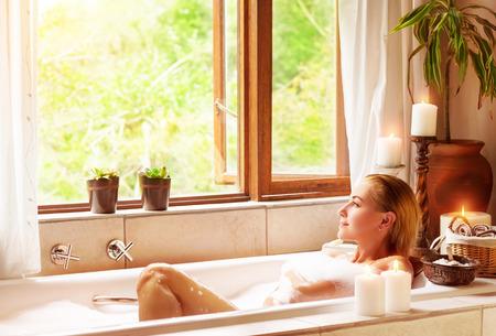 mujer bañandose: Baño de la mujer con el placer, tumbado en la bañera con espuma y mirando en la ventana, pasar tiempo en el balneario de lujo Foto de archivo