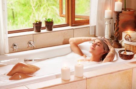 relaxando: Mulher que relaxa no spa resort, deitado na banheira com os olhos fechados e fazer uma compressa, prazer e estilo de vida saudável