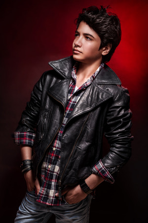 cool guy: Handsome boy portrait over red background, wearing leather jacket and stylish shirt, fashionable autumn clothes, funky teens fashion