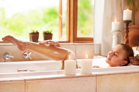 Rozostřený fotografie jemné mladé ženy vleže ve vaně s pěnou a svíčku, se těší lázeňskou procedurou v luxusním letovisku Reklamní fotografie