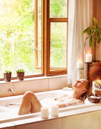 mimos: Baño de la mujer feliz, acostado en la bañera con los ojos cerrados de placer, relajación en el balneario de lujo, estilo de vida saludable