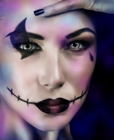 beldam: Primo piano ritratto di donna con il trucco per Halloween partito su sfondo blu scuro, terrificante strega, zombie morto guardare