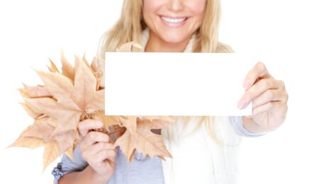 isolated woman: Smiling woman holding in hands dry leaves and greeting card with copy space isolated on white background, face part, soft focus, congratulations on the advent of autumn concept