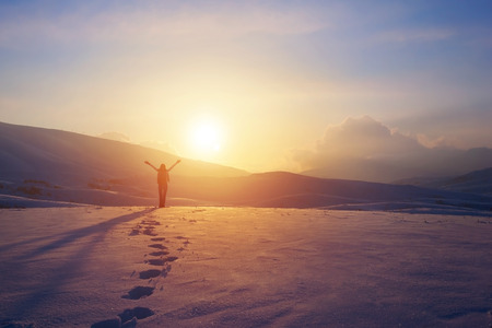 woman hands up: Happy joyful woman having fun outdoors in winter, standing on the mountains with raised up hands on the mountain covered with snow, enjoying beautiful sunset