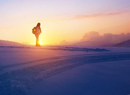 snow white: Woman enjoying beautiful sunset view from the high snowy mountain, discovering wild nature, active winter holidays Stock Photo