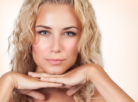 Closeup portrait of gentle female with perfect clear skin over beige background, healthy lifestyle, luxury beauty salon