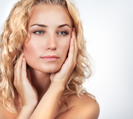 skin care woman: Portrait of beautiful gentle blond woman over light background, using natural cosmetics in spa salon, beauty treatment